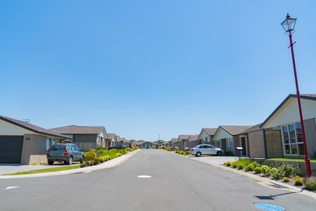 Nouvelle rue de lotissement avec des maisons uniformes et des jardins à l'avant bordant les deux côtés de la rue.