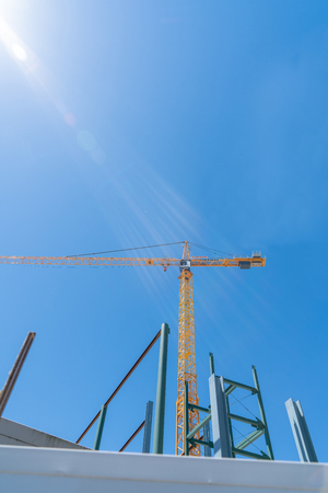 Tauranga, New Zealand - October 27 2019; Redevelopment of Farmer's building site with excavation and foundations for new building  and tall yellow crane Editöryel