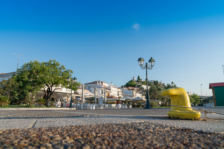 Skiathos Greece - July30 2019; Empty street, empty seating on Paralaikos, the waterfront promenade with yellow bollard on Greek Island Skiathos. 에디토리얼