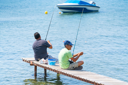 Skiathos Greece 6 August  2019; Two hopeful men sitting on small jetty fishing