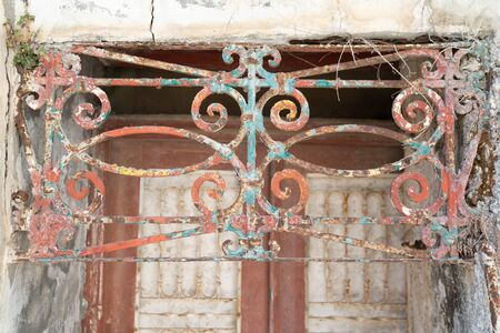Rusty painted old ornate decorative wrought iron grill in front of door in dilapidated state. 版權商用圖片