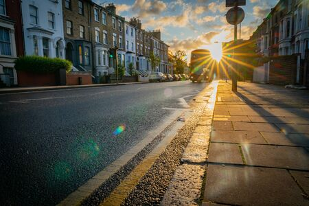 London, England - August 17 2019; Looking into sun burst along Graham Road as bus approaches in hazy morning light. Stockfoto - 138004268