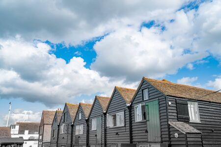Black row of terrace style holiday homes from converted boatsheds in Whitstable, England.