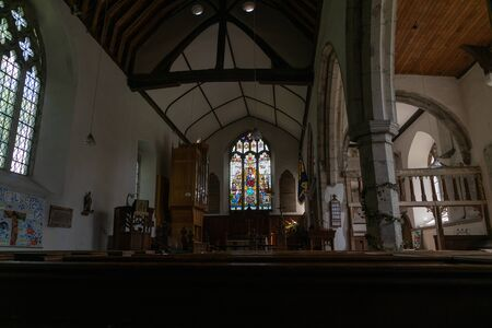 Inside dimly lit historic Christian church in United Kingdom.
