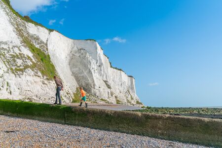 Dover England - August 19 2019; Man and boy walk from beach towards face of White Cliffs of Dover.