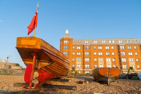 Stern view of two classic old-fashioned boats pulled up on stony beach with large red brick apartment building in background glowing in light from sunrise at deal in United Kingdon. Stock Photo