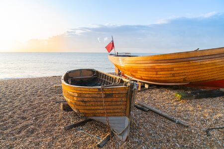 Two varnished traditional style clinker boats pulled up on beach sitting on chocks and catching the sunrise on their hulls.