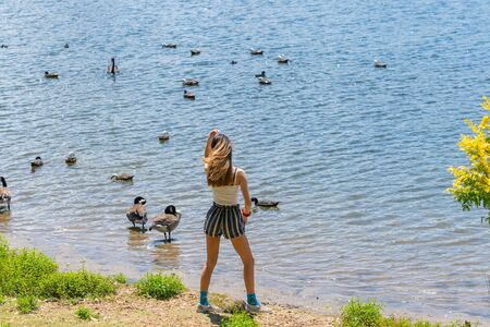 Young woman standing, stepping of moving at waters edge by lake with ducks on water.