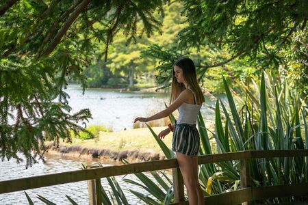 Teenage girl standing in shadows with arms slightly raised in calm zen like way by  railing looking  to lake and bush beyond in McLaren Falls Park, Tauranga New Zealand. Banco de Imagens