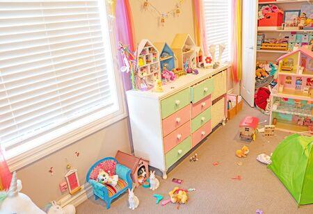 All'interno di una cameretta disordinata ma ben usata di una bambina con giocattoli e cose sparse e ante dell'armadio aperte.