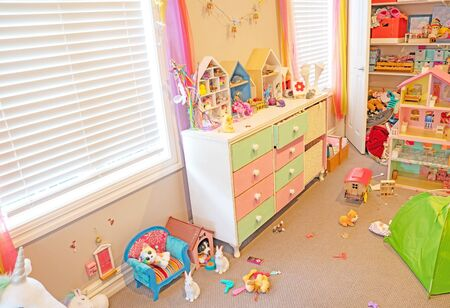 Inside a messy but well used small girl's bedroom with toys and things scattered about and cupboard doors open. Archivio Fotografico