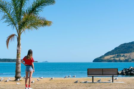 Teenage girl standing near palm tree looking across Tauranga Harbour with landmark Mount Maunganui in background on horizon.