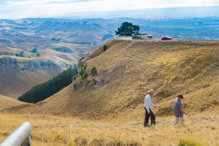 Hastings New Zealand - February 16 2020; Two mature men with hats walking on Te Mata Peak in Hawkes Bay, New Zealand, landscape view across surrounding hills and Heretaunga Plains