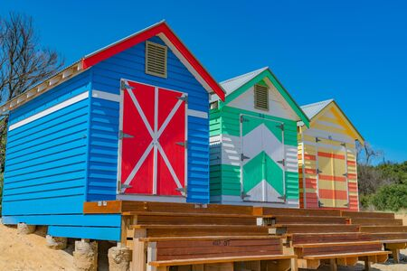 Steps leading to doors of colourful Brighton Beach Boxes on beach at Melbourne, Australia.