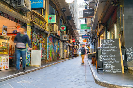 Melbourne Australia - March 14 2020; Quiet early morning movement in narrow laneway of Degraves Street with shops and cafe signs and blackboard offerings,