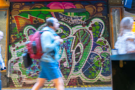 Melbourne Australia - March 10 2020; Blurred shapes of people walking through Centre Place Laneway before all cafes and shops open pats closed roller door with street art.