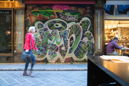 Melbourne Australia - March 10 2020; Blurred shapes of people walking to work through Centre Place Laneway before all cafes and shops open pats closed roller door with street art.