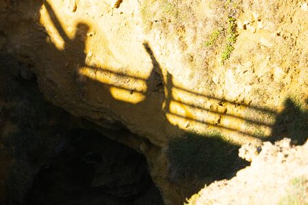 Shadow pattern of railing and people walking down to The natural arch and bridge of The Grotto geological formation that attracts tourists along Great Ocean Road in Victoria Australia.
