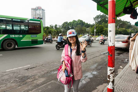 Saigon Vietnam - October 12 2013; Young Vietnamese woman in trendy cap and clothes smiles and wave on  city street