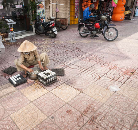 Saigon Vietnam - October 12 2013; Egg vendor Woman in conical hat sitting on low stool on city pavement checking and selling eggs for a living in Saigon, Ho Chi Min City. Éditoriale