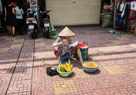 Saigon Vietnam - October 12 2013; Woman selling and eating corn in conical hat sitting on low stool on city pavement checking and selling eggs for a living in Saigon, Ho Chi Min City.