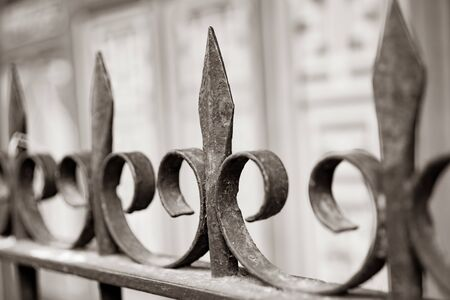 Wrought iron gence spikes and decorative curl shapes close up in selective focus. in monochrome. Stok Fotoğraf