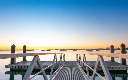 Leading lines of pier rails to water and sunrise