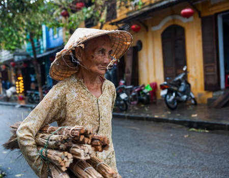 Hoi An Vietnam October 17 2020; Old woman with face showing lines of hard life wearing a tatty conical hat and carrying load of bundles of cane.