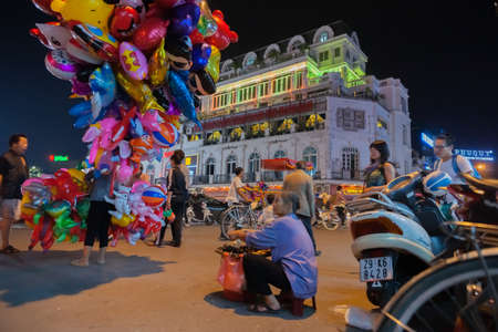 Hanoi Vietnam - October 21 2013; Street scene in city at night long exposure with blurs of hustle and bustle of moving people in long exposure image. Editöryel