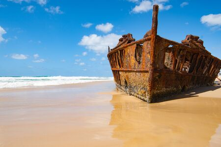 Fraser Island, Maheno shipwreck rusting away on beach under blue sky..