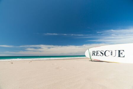Hawaii USA October 31 2014; Hawaiian sandy beach with RESCUE sign on surfboard on sand with sea and blue sky beyond.1