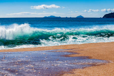 Surf waves crash in on Tairua beach on Coromandel Peninsula, New Zealand closeup. Reklamní fotografie
