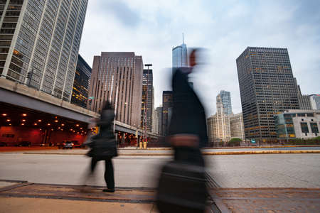 Pedestrians close by blurred as they walk by in street scene, at  East Upper Whacker and Columbus Drive tiered road and highrise buildings, Chicago, Illinois, USA