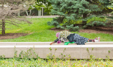 Chicago USA - August 29 2015; Rough sleeping person wrapped in old rugs asleep on concrete beams in city park Редакционное