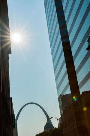 St Louis Gateway Arch at end of city street framed by high-rise buildings with sunburst. St Louis, architecture, and famous arch, Missouri,USA. Stockfoto
