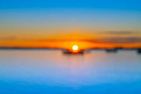 Abstract deliberate defocus coastal background for travel or coastal effects use sunrise over blue water of Tauranga harbour with intense golden glow on horizon.