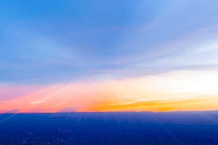 Abstract sky and city light below in zoom blur at sunset across New Mexico landscape from Sandia Peak, Albuquerque, New Mexico, USA.
