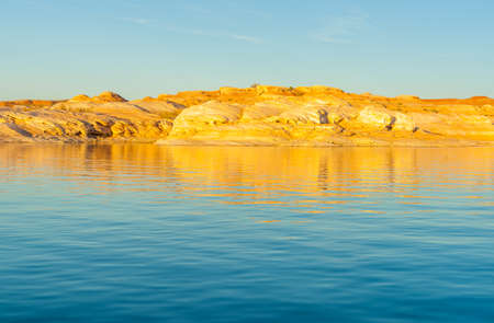 As sunsets light hits the rock embankments with a golden glow on other side Lake Powell a man-made reservoir on the Colorado River in Utah and Arizona, United States. Foto de archivo