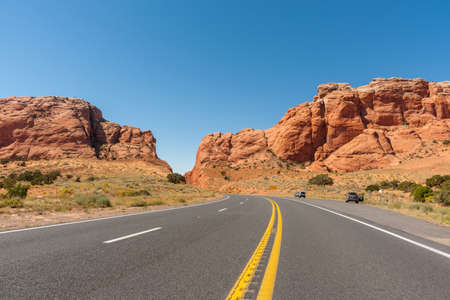 Roadtripping through Arizona on the highway running between two giant red rock bluffs.