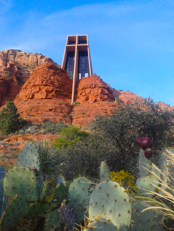 The Chapel of the Holy Cross architectural chapel built into rock face above desert vegetaion of prickly pear catcus in Sedona Arizona.