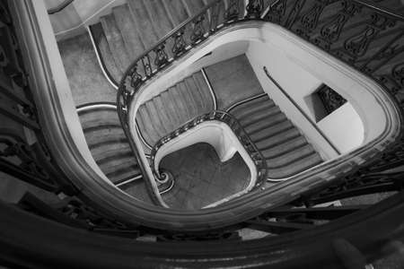Spiral staircase winding down to ground floor in Spanish Colonial Revival architectural Styles emphasised by night lighting
