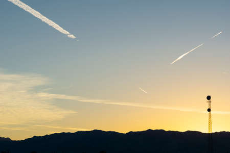 Communication tower stands alone of silhouette land below sunset sky of golden glow and blue with white jet trails crossing.