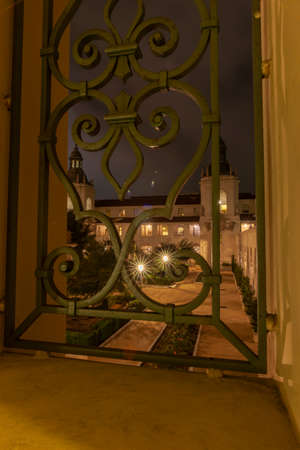 Star bursts across courtyard through ornate wrought iron gate Mediterranean and Spanish Colonial Revival architectural Styles emphasised by night lighting