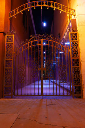 Ornate wrought iron gate under festive night lights at entrance of alleyway.