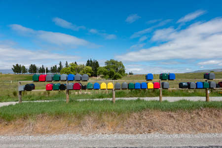 Rows if multi-coloured rural lexxterboxes on country road.