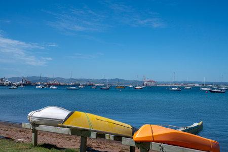 Three dinghies on rack in bay with Tauranga harbor background. 版權商用圖片
