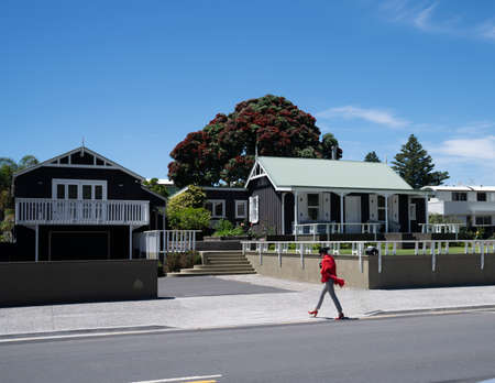 Stylish woman in red top and shoes walks across footpath and past two quaint black cottages with green roof.