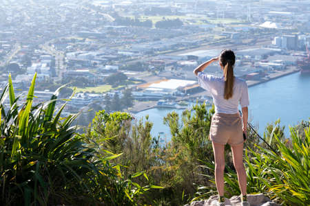 Teenage woman standing on summit of Mount Maunganui sheilding eyes and looking at view of town and harbour below.