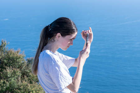 Teenager on top Mount Maunganui checking device while shading screen with blue ocean behind. 版權商用圖片