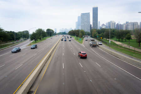 Highways leading in Chicago with highrise buildings ahead and vehicles blurred in motion entering and exiting city, Illinois, USA